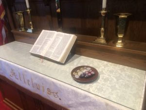 Communion elements individually wrapped and packaged on altar near Bible.